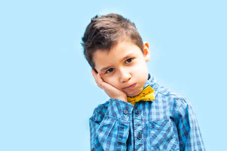 portrait of a boy on a blue background. The boy has a toothache