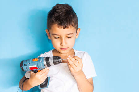 little boy learns to work with a screwdriver. Craftsmanship lessons with tools