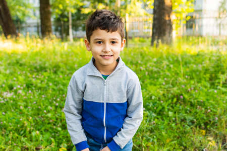 portrait of a 6 year old boy in the park in summer