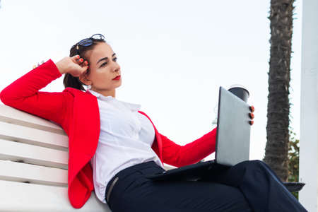 business woman with laptop sitting on a bench