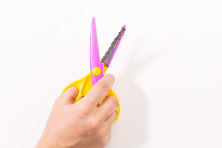 curly paper scissors in hand on a white background
