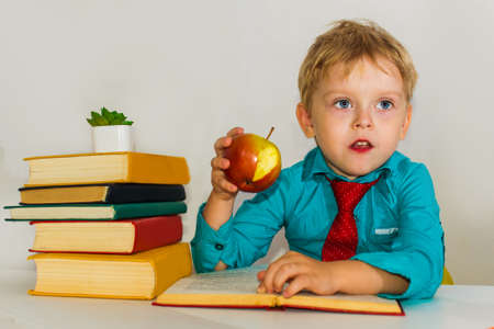 preschool boy at the Desk eating an apple. snack during classes. Reklamní fotografie