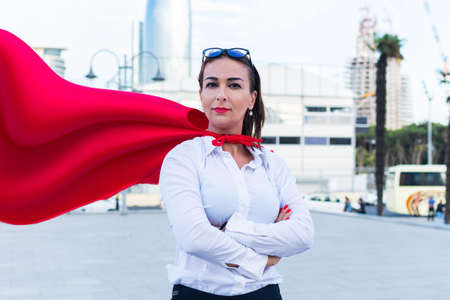 business successful woman with a superhero cape on the background of the city Reklamní fotografie