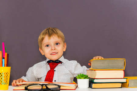 serious preschool boy at the table with books on a gray background