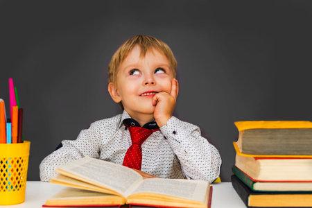 pensive preschool boy sitting at a Desk. Blond boy does his homework