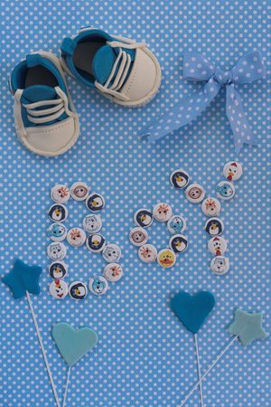 Boy sign with kids buttons on  blue polka dots background. Baby announcement. Fondant accesories. Baby shower idea. Stock Photo