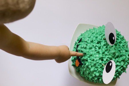 I want that cake. Curious baby boy points with his finger on interesting frog cake.Yummy. Overhead view