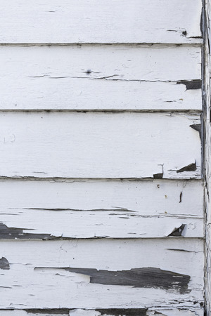 old wooden weatherboard wall with peeling white paint. Stock Photo