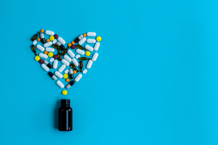 Pills,capsules and tablets  arranged in heart shape on a blue background.Spilled pill bottle. Concept of health, treatment, choice, healthy lifestyle. Copy space advertisement