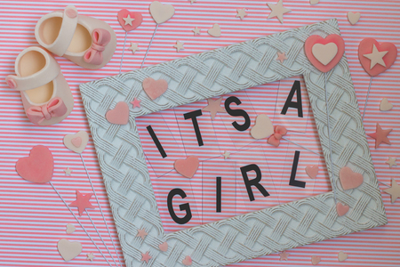 Sweet baby shoes and its a girl sign in a frame decorated with accessories made from fondant. Newborn background. Baby shower announcement. Flat lay