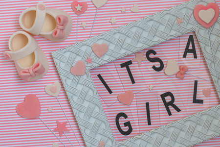 Its a girl sign in a frame decorated with accessories made from fondant. Newborn background. Baby shower announcement. Stock Photo