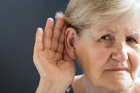 Elderly woman with hearing problem on grey background. Age-related hearing loss, symptoms and treatment concept.