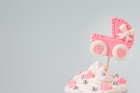 It's a girl cupcake, close up. Newborn background. Baby shower invitation. Baby announcement. Fondant baby accessories. 免版税图像