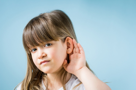 Child with hearing problem on blue background. Hearing loss in childhood, symptoms and treatment concept. Close up, copy space. Stock Photo