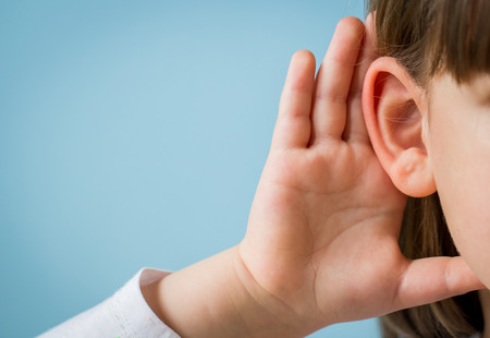 Child with hearing problem on blue background. Hearing loss in childhood, symptoms and treatment concept. Close up, copy space. Standard-Bild