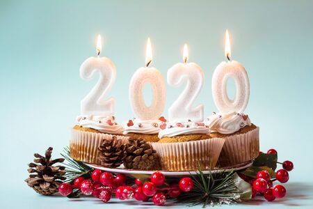 Happy New Year 2020 cupcakes with lighting candles on blue background. Merry Christmas and winter season greetings concept. Copy space