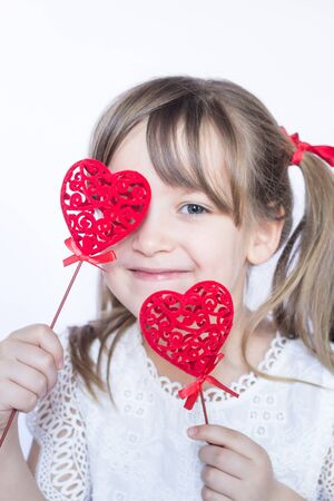Two decorative hearts holding by the cheerful girl child on white background. Happy childhood and love concept. Close up.