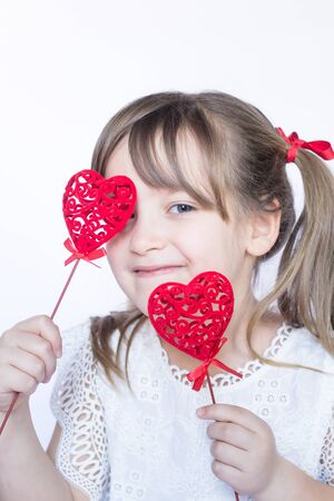 Smiling  girl kid holding two decorative red hearts on a stick on white background. Happy childhood and love concept. Copy space.