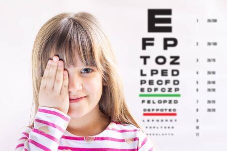 Linda chica visitando al médico de los niños. Examen de la vista. Prueba de Oftalmología.