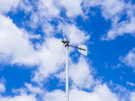 wind turbine against partly cloudy blue sky ,energy conservation concept