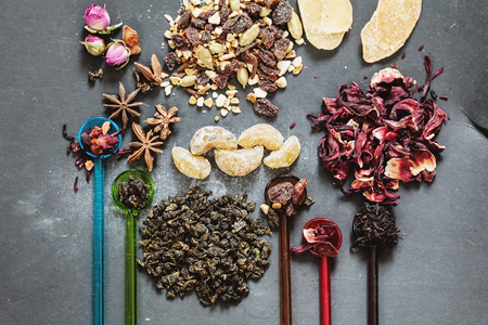 oolong: Oolong tea, hibiscus and dried amla, ginger, roses, citron and cinnamon on the dark grey background