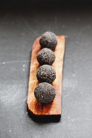 carob: Row of raw vegan sweet candy balls with carob and poppy seeds Stock Photo
