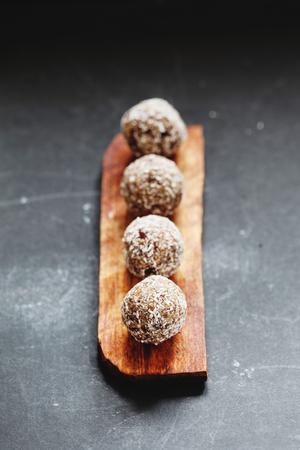 carob: Row of raw vegan sweet candy balls with carob and coconut