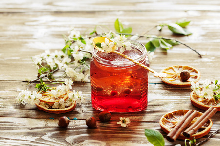 Layered homemade marmalade on the wooden background with cherry flowers, selective focus