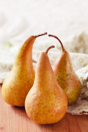 bosk: Fresh ripe organic pears on a rustic wooden table, selective focus close up