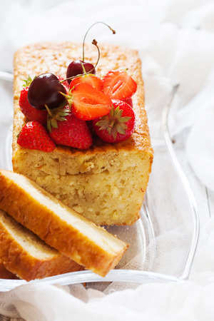 Fruitcake with strawberry and cherry topping on the old white wooden table, selective focus Stock Photo