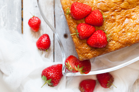 Piece of sponge cake with strawberry topping on the old white wooden table, top view