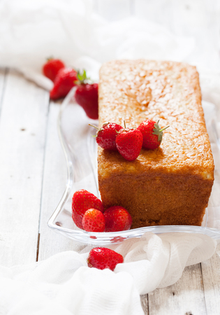 pound cake: Sponge cake with strawberry topping on the old white wooden table, selective focus Stock Photo