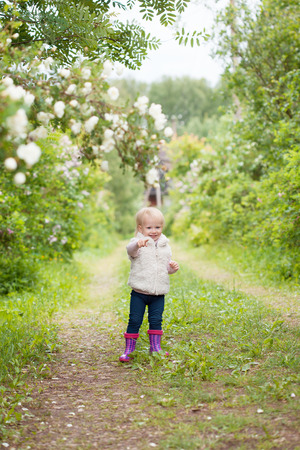 12 year old: Cute baby girl with blonde hair in the blooming garden outdoors. Little girl 1-2 year old. Stock Photo