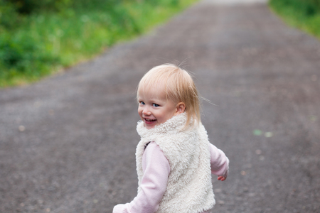 12 year old: Cute baby girl with blonde curly hair running outdoors. Little girl 1-2 year old.