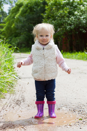 2 year old: Happy smiling portrait of a 2 year old blonde girl playing in the puddles on nature