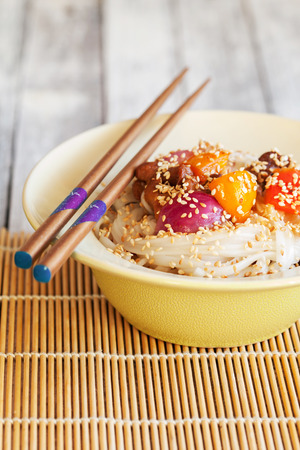 Udon noodles with chicken, vegetables and sesame, close-up