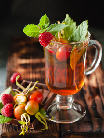 Rosehip tea with raspberry and currant leafs in glass on black stone background, concept of vitamin drink Stock Photo