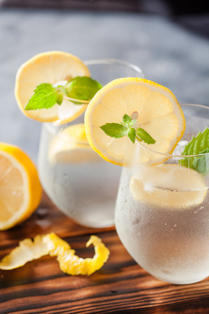 Sparkling lemonade with lemon and mint on dark background Stock Photo