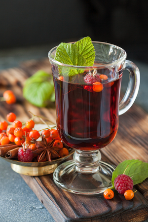 Ashberry and raspberry tea, autumn concept. A cup of hot tea flavored with cinnamon and anise