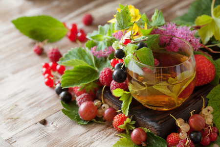 Hot herbal tea with fresh summer berries and herbs on rustic background