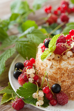 Homemade honey cake with sour cream garnished with fresh berries on a wooden table