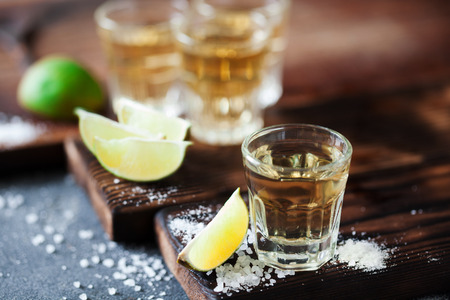 Tequila golden with lime and sea salt decorated with blackberry and mint on the dark background