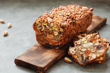 Traditional healthy fruit cake with nuts for on wooden board over black slate background Фото со стока - 85318825