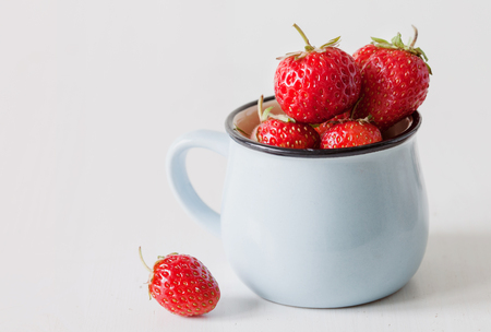 Fresh garden strawberry in blue enameled mug on old wooden background, copy space Stock Photo
