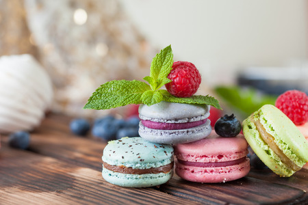 Assorted sweets, macarons, chocolate cake and Marshmallows with mint and fresh berries close up
