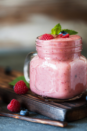 red straw: Well being and weight loss concept, berry smoothie with fresh raspberry and blueberry