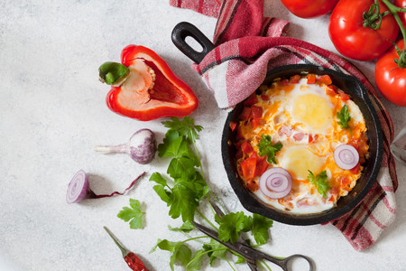 Shakshuka in a cast iron pan, traditional middle eastern traditional dish. Fried eggs with vegetables. Top view with space for text