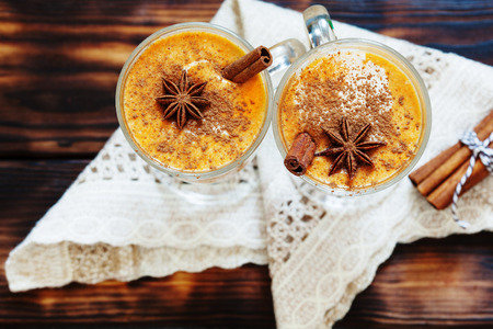 Pumpkin spice latte, hot coffee drink with pumpkin and cinnamon top view