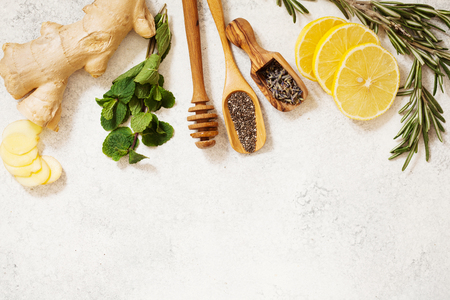 Organic ingredients for detox healthy drink. Mint, rosemary, honey, ginger, lemon, chia and lavender seeds top view with place for text