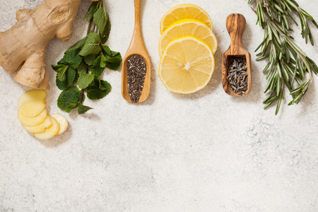Organic ingredients for detox healthy drink. Mint, rosemary, honey, ginger, lemon, chia and lavender seeds top view with place for text Stockfoto